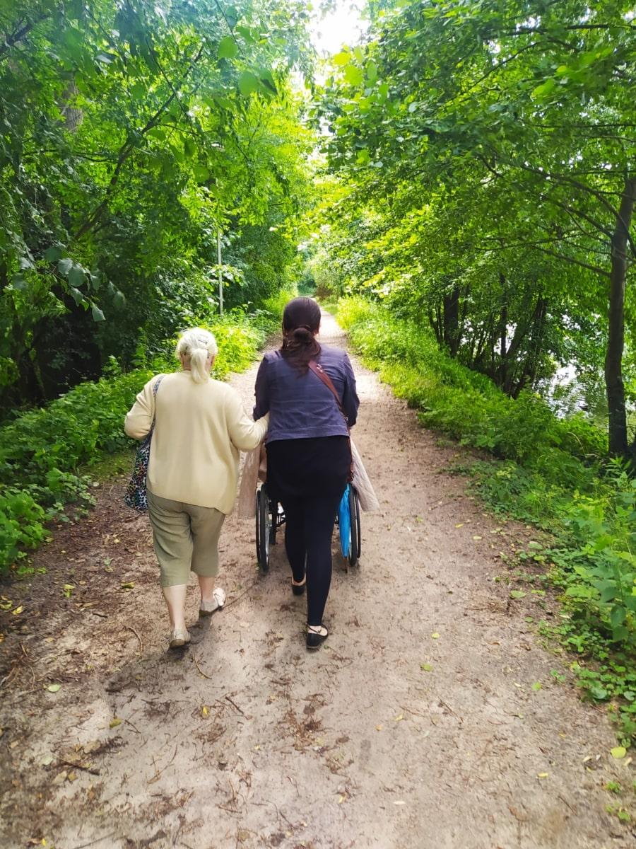 Zdjęcie przedstawiające dwie spacerujące osoby wlesie